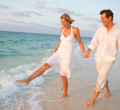 Couple walking on the beach by the water